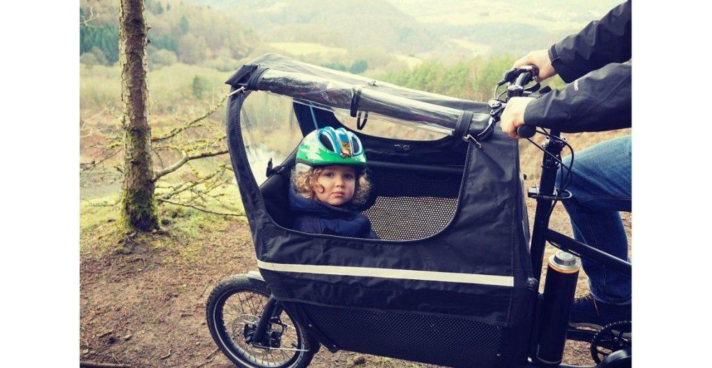 e-Lastenrad muli cycle Regenverdeck über Ladekorb mit Kindersitz