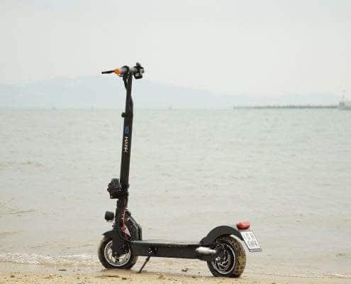 E-Scooter IO Hawk Exit-Cross steht an einem Strand